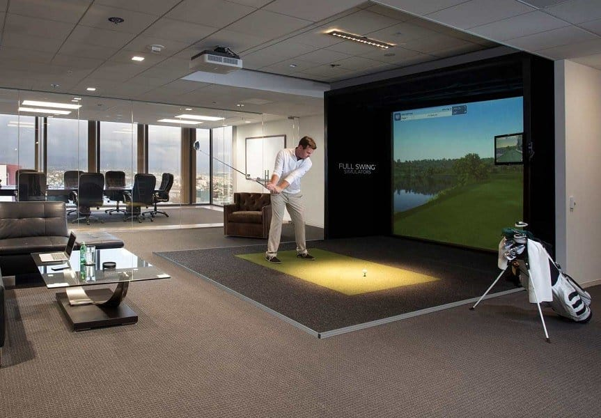 Man practicing golf at home with the simulator