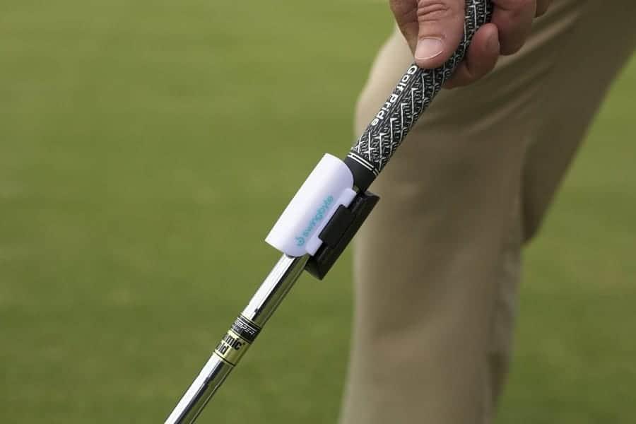 Man preparing to swing, golf analyzer mounted on club