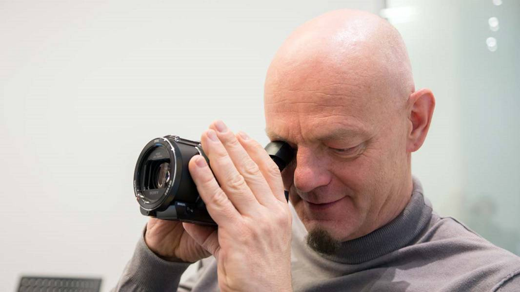 Image of a man smiling while filming with a 4K camcorder