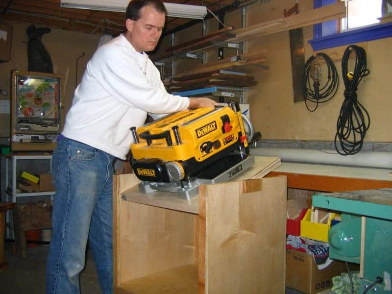 Man flipping bench over to use his benchtop planer
