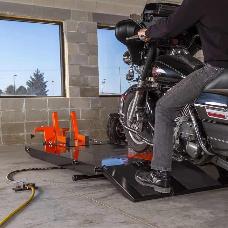 Man loading the motorcycle onto a lift table Image