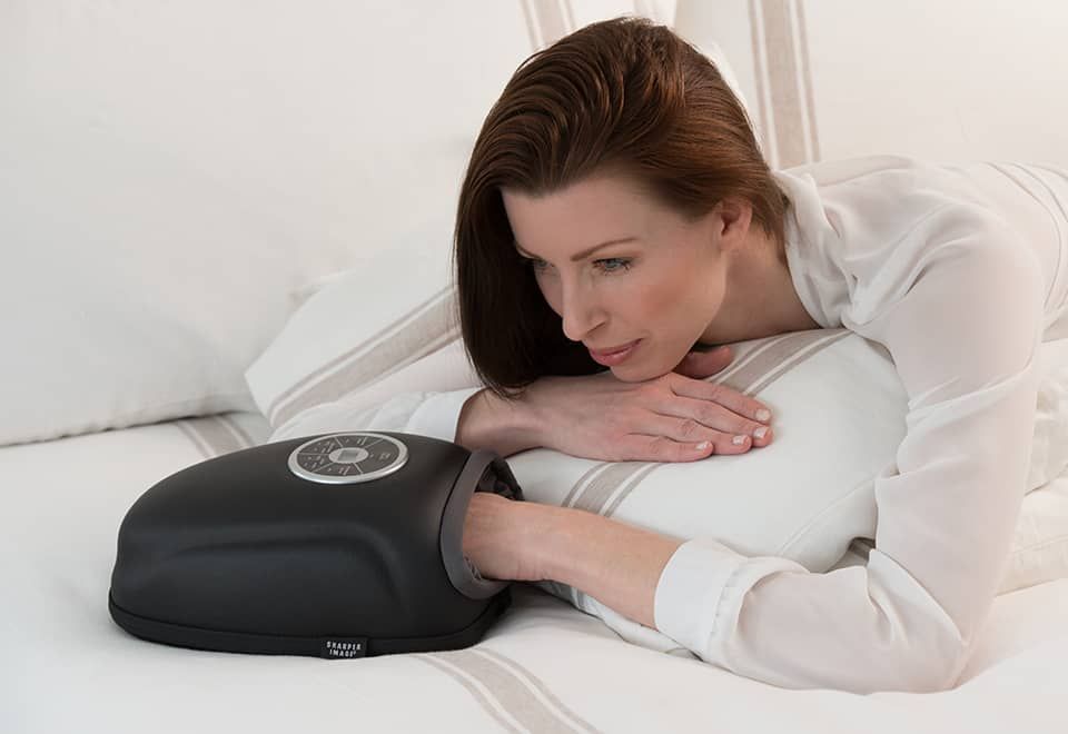 Woman getting a hand massage from a hand massager device while lying in bed